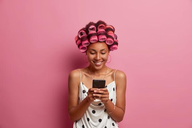 Mujer de piel oscura positiva aplica rulos para hacer un peinado perfecto sostiene un teléfono móvil moderno