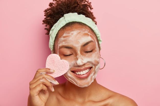 Mujer de piel oscura positiva con cabello afro peinado, usa diadema, se preocupa por la piel del rostro, limpia las mejillas con una esponja cosmética, mantiene los ojos cerrados con placer