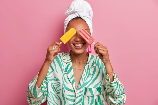 La mujer de piel oscura positiva cubre los ojos con helados frescos y fríos, se divierte durante el día caluroso, usa una bata doméstica informal y una toalla de baño después de tomar una ducha