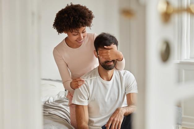 Mujer de piel oscura positiva cubre los ojos de su marido