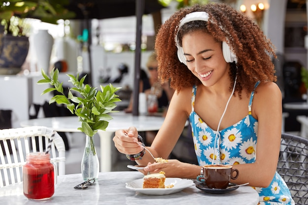 Mujer de piel oscura positiva escucha música de la lista de reproducción en auriculares, come un delicioso postre con café, pasa el tiempo libre en un acogedor café