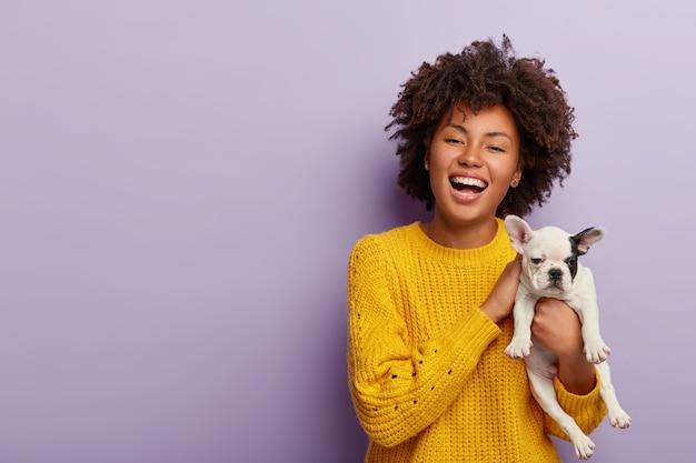 Mujer de piel oscura positiva inspirada disfruta de la compañía de sus mascotas