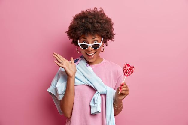 La mujer de piel oscura positiva tiene el pelo rizado, sostiene una paleta, se divierte con sus amigos durante el día libre, usa gafas de sol, le gustan los dulces, posa