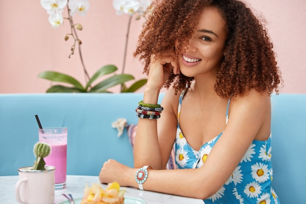 Mujer de piel oscura rizada joven bastante positiva en camiseta azul de verano, tiene expresión feliz mientras pasa tiempo libre en la cafetería con cóctel fresco