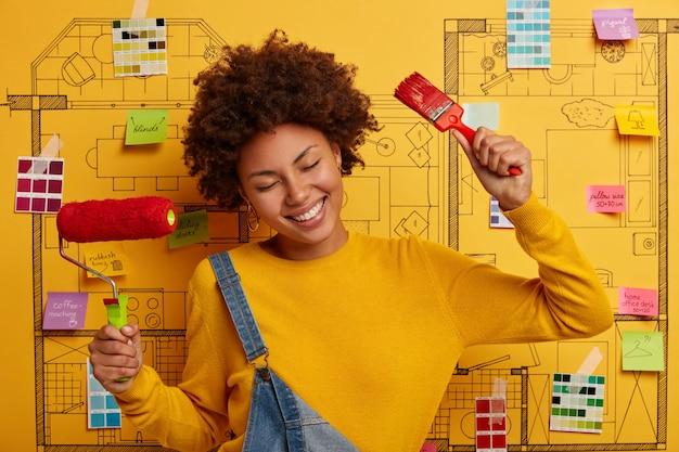 Mujer de piel oscura satisfecha se para con herramientas de pintura, tiene una expresión alegre, se viste informalmente, imagina su habitación perfecta