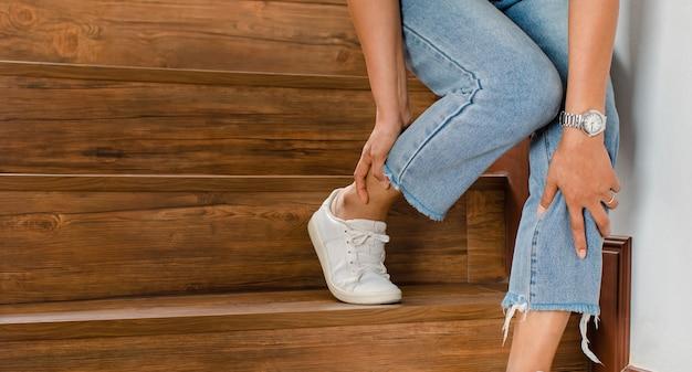 La mujer pierde el control y no puede caminar por las escaleras, se detiene y sostiene las piernas para apoyarse y descansar con una sensación de hormigueo. concepto de síndrome de guillain barre y enfermedad de piernas entumecidas o efecto secundario de la vacuna.