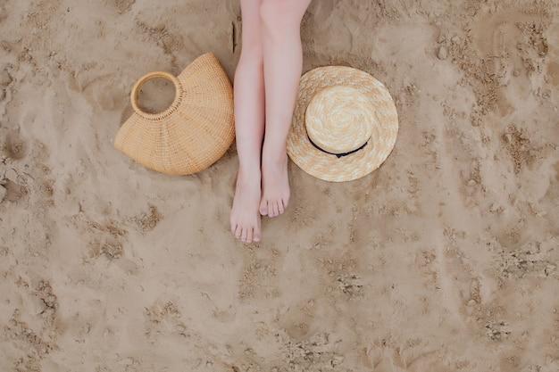 Mujer piernas bronceadas, sombrero de paja y bolsa en la playa de arena. relajarse en una playa, con los pies en la arena.