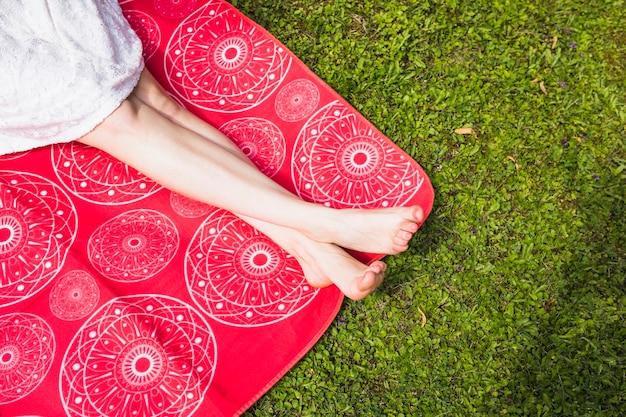 Mujer con las piernas cruzadas sentado en una manta roja sobre la hierba verde