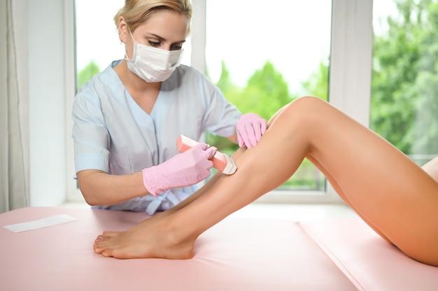 Mujer con piernas largas y bronceadas perfectas y piel lisa con depilación de rayas de cera