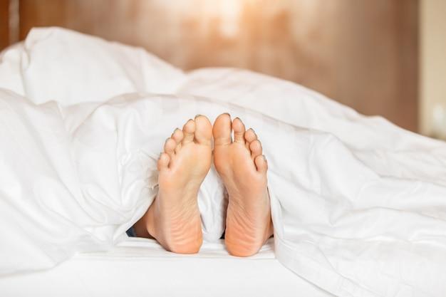 Mujer pies bajo manta blanca vista lateral