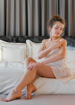Mujer en pijama en casa aplicando loción en el cuerpo