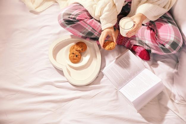 Mujer en pijama leyendo un libro y bebiendo leche con galletas en su cama