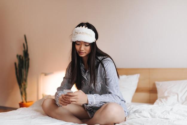 Mujer en pijama y lindo antifaz para dormir está sentada en la cama y charlando en el teléfono