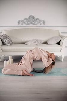 Mujer en pijama sentada en la alfombra y haciendo flexión hacia atrás durante los ejercicios por la mañana en casa. concepto de estilo de vida saludable. fitness matutino