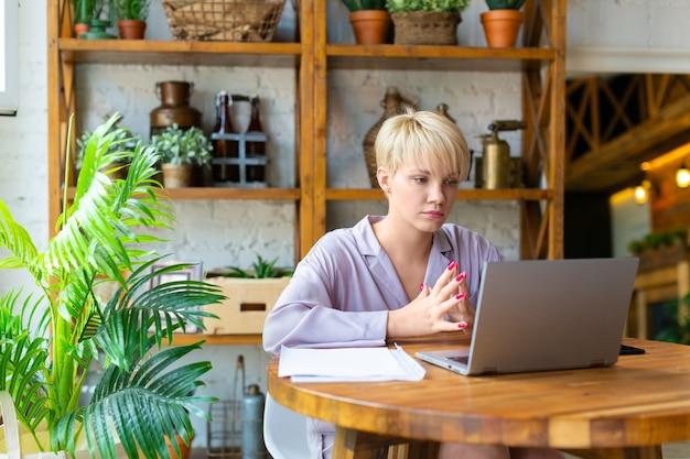 Mujer en pijama trabaja con documentos frente a un monitor de computadora portátil en el interior de una casa