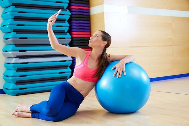 Mujer de pilates dispara autorretrato autofoto móvil.