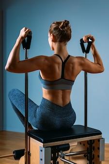 Mujer de pilates en un reformador haciendo ejercicios de estiramiento en el gimnasio