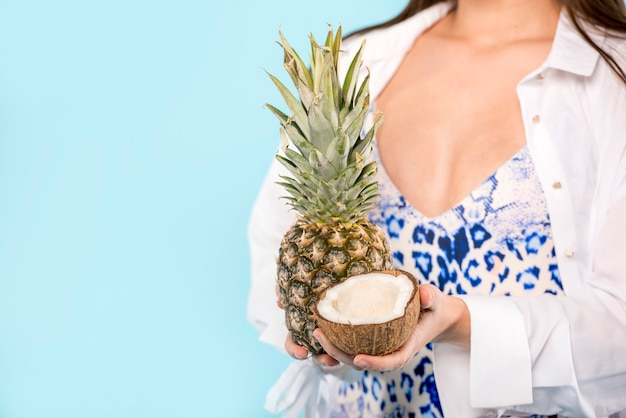 Mujer con piña y coco