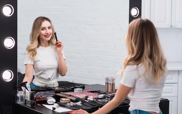 Mujer con pincel para maquillaje de pie en el espejo