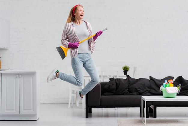Mujer con pincel saltando en casa