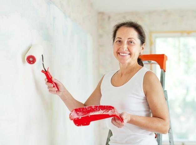 La mujer pinta la pared con el rodillo