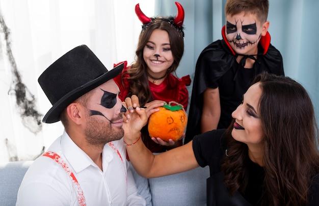 Mujer pintando la cara de su esposo para halloween
