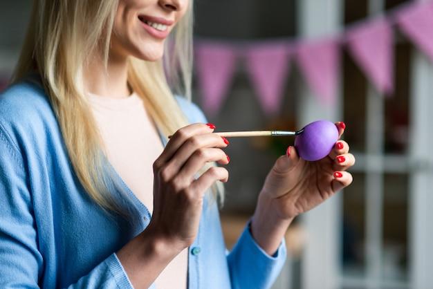 Una mujer está pintando un huevo de pascua, vista de primer plano.