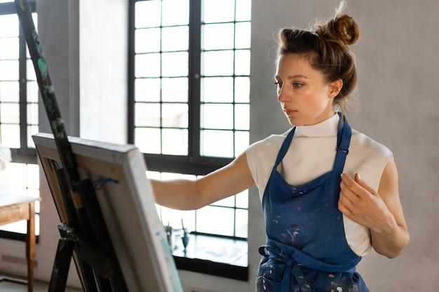 Mujer pintando en interiores plano medio