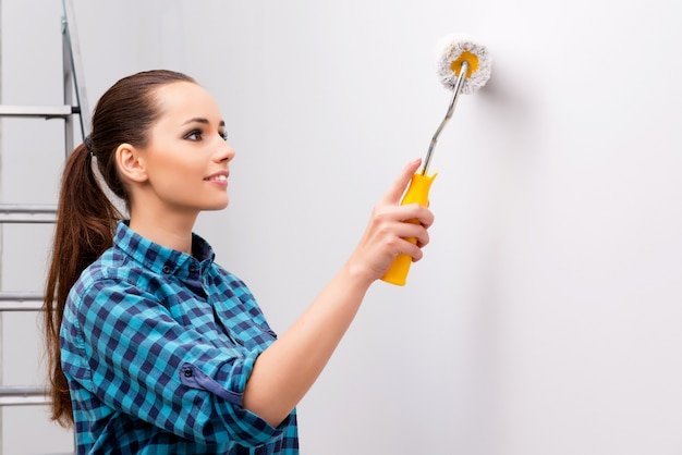 Mujer pintando la pared en concepto de bricolaje