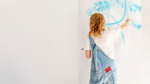Mujer pintando una pared con espacio de copia
