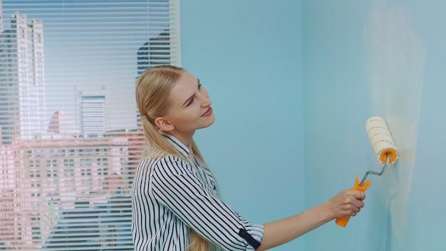 Mujer pintando una pared en la oficina.