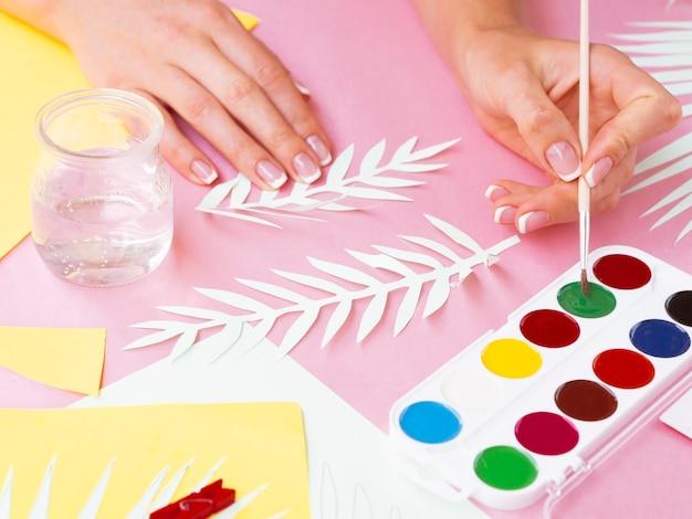 Mujer pintando ramas de árbol de papel