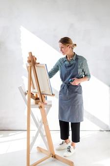 Mujer pintando sobre lienzo en estudio