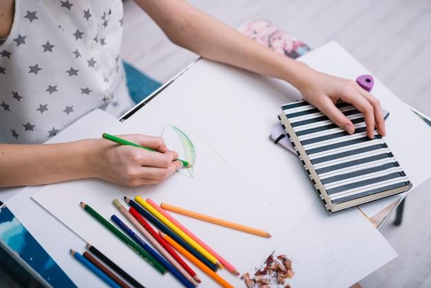 Mujer pintando sobre papel en mesa con set de lápices y cuaderno