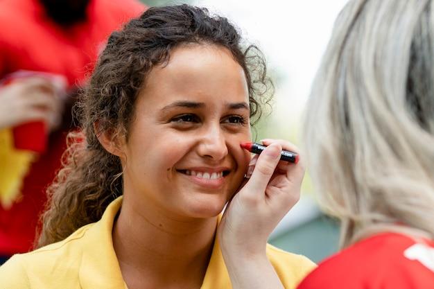 Mujer pintando sus mejillas con los colores de su equipo