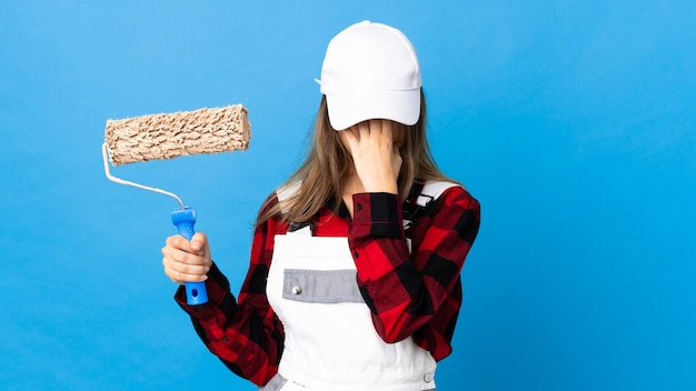 Mujer pintor sobre pared azul aislada con expresión cansada y enferma
