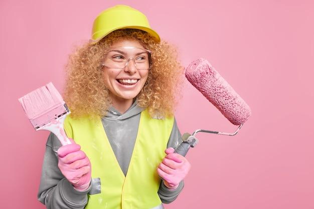 Mujer pintora satisfecha con el resultado de su trabajo lleva gafas de seguridad y uniformes protectores para la cabeza