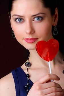 Mujer con piruleta roja en forma de corazón