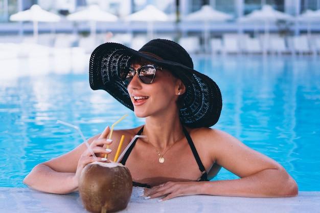 Mujer en la piscina bebiendo leche de coco