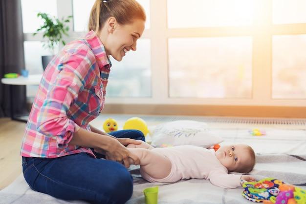 Una mujer en el piso de la sala de estar y juega con el niño.