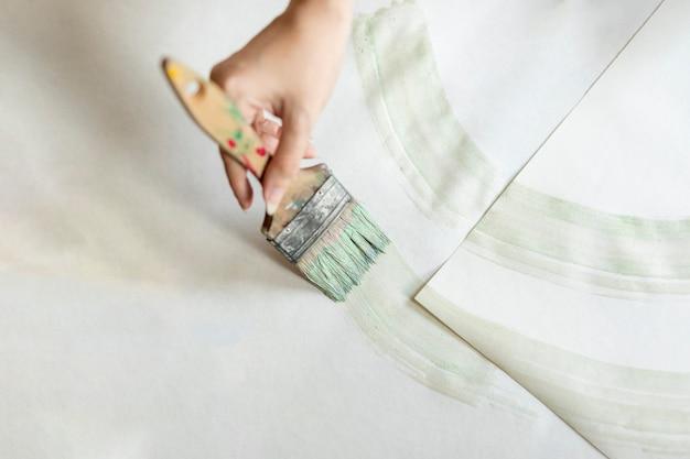Mujer plana endecha pintando en el piso