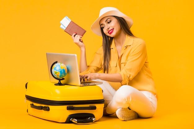 Mujer planeando un viaje en la computadora portátil mientras sostiene boletos de avión y pasaporte