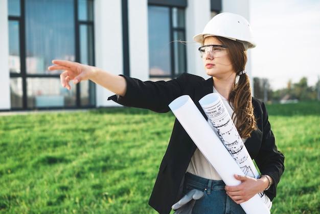 Mujer con planos señalando