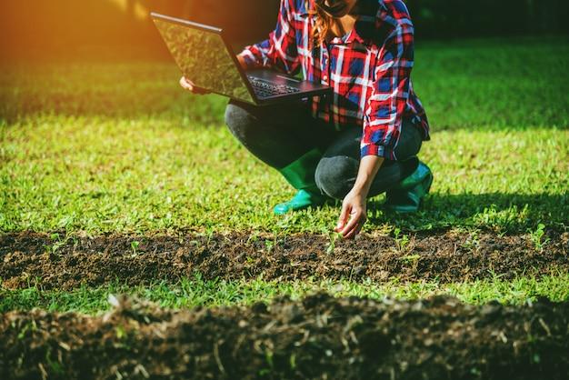 Mujer planta hortalizas en el jardin