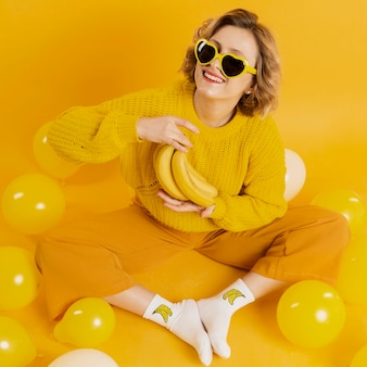 Mujer con plátanos y globos amarillos