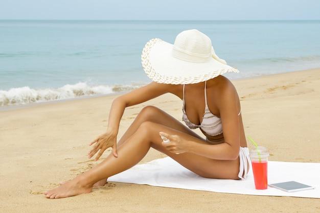 Mujer en la playa aplicando spray protector solar en su cuerpo