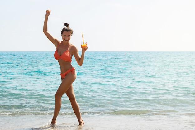 Mujer en la playa con una copa de cóctel