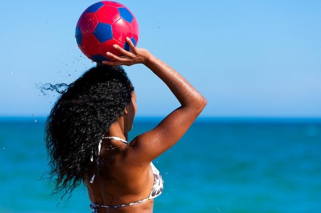Mujer en la playa jugando futbol