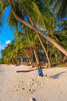 Mujer en la playa monta en un columpio durante el atardecer. puesta de sol en el trópico, disfrutando de la naturaleza. columpio atado a una palmera por el océano