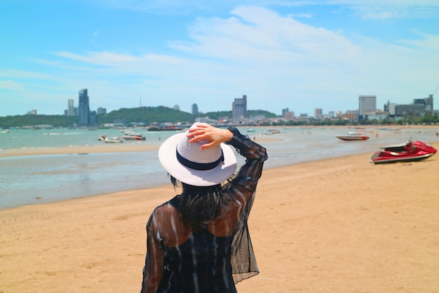Mujer en la playa del sol mirando el mar
